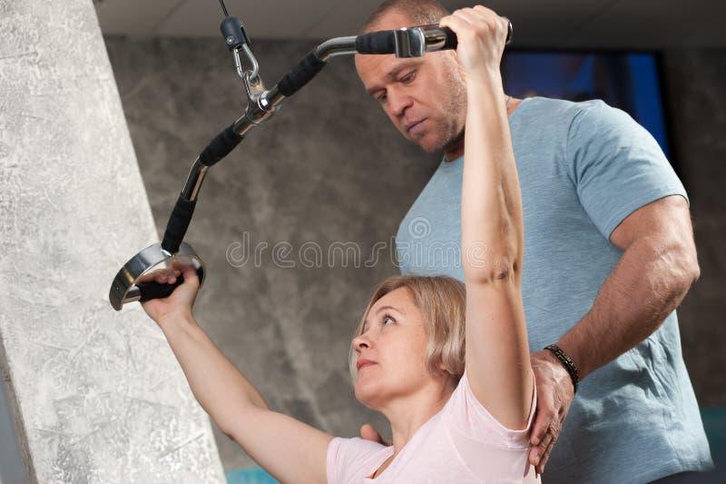 Мужской тренер показывает как сделать тренировки стоковое фото