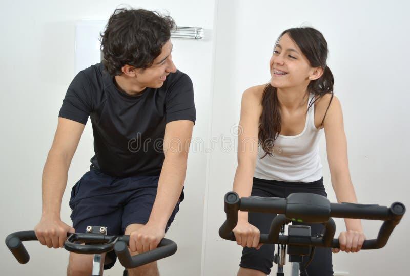 Мужской тренер фитнеса помогая молодой студентке делая тренировку стоковые фотографии rf