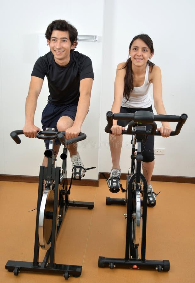 Мужской тренер фитнеса помогая молодой студентке делая тренировку стоковая фотография rf