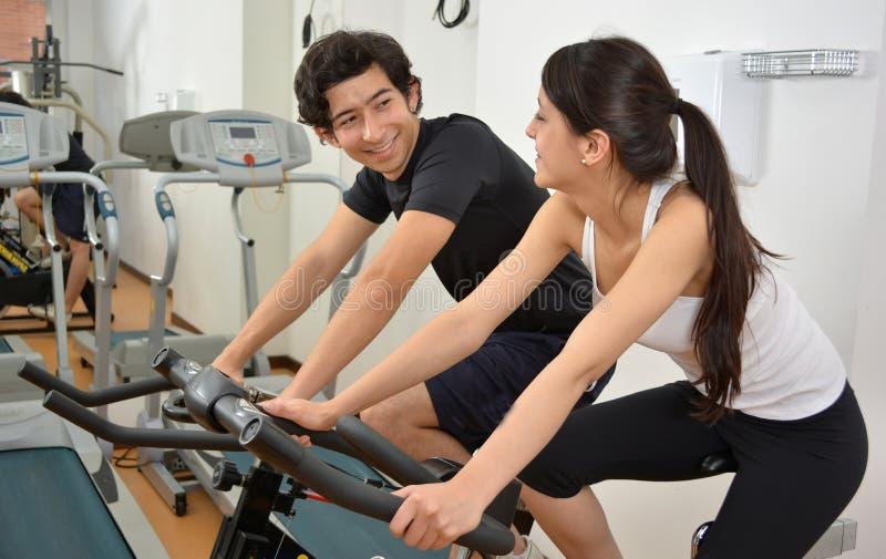 Мужской тренер фитнеса помогая молодой студентке делая тренировку стоковое изображение rf