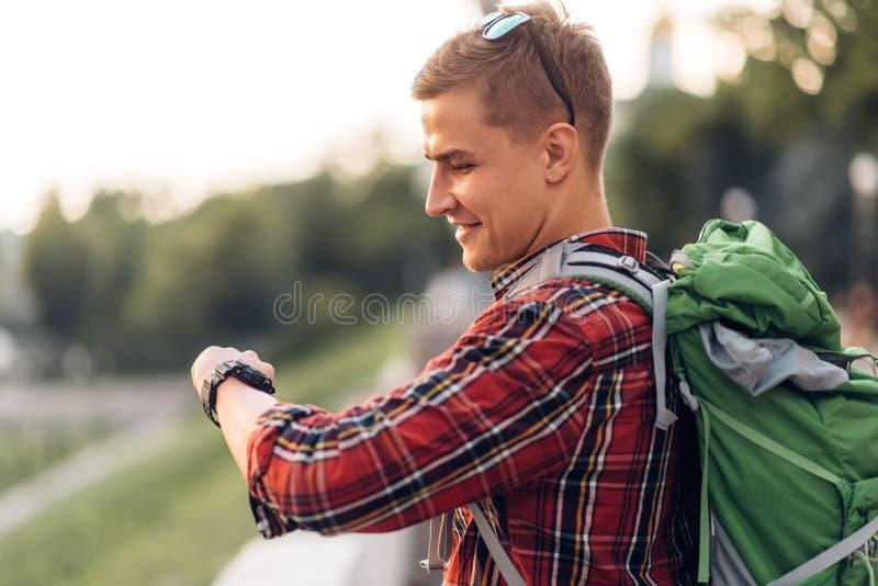 Мужской турист с рюкзаком смотря часы стоковые изображения rf