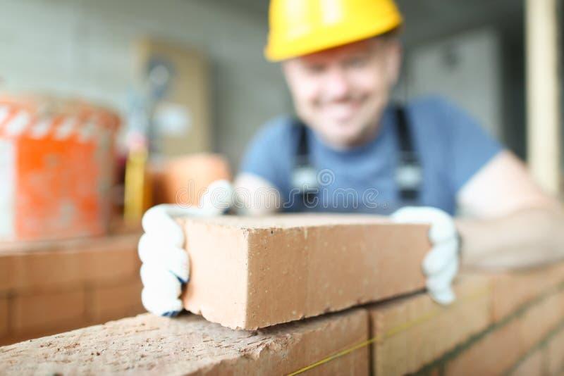 Мужской усмехаясь построитель кладет для того чтобы сделать кирпичную кладку стоковые изображения rf