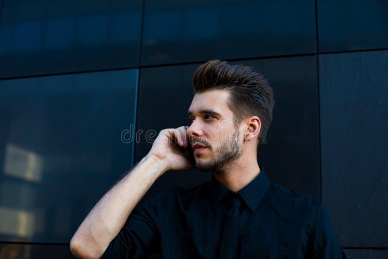 Мужской успешный предприниматель имея разговор смартфона, смотря прочь Парень хипстера вызывать стоковая фотография rf
