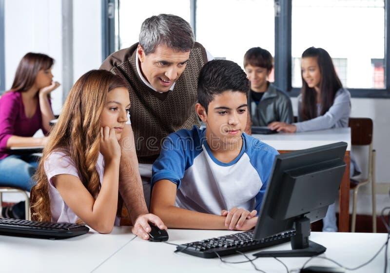 Мужской учитель помогая студентам в классе компьютера стоковое изображение