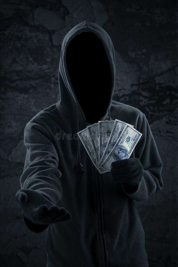 Мужской уличный вор принимая доллары денег стоковая фотография