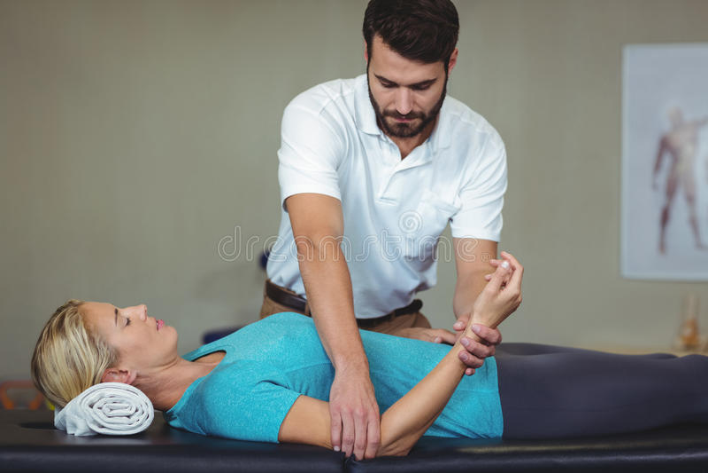 Мужской физиотерапевт давая массаж руки к женскому пациенту стоковое изображение