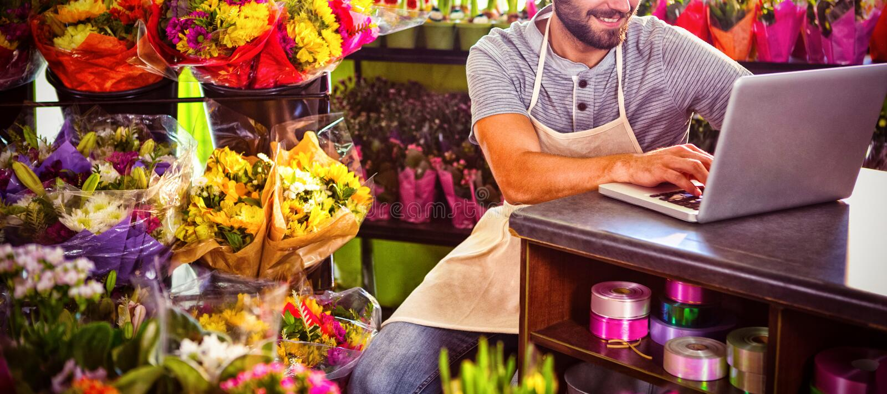 Мужской флорист используя компьтер-книжку стоковое изображение rf