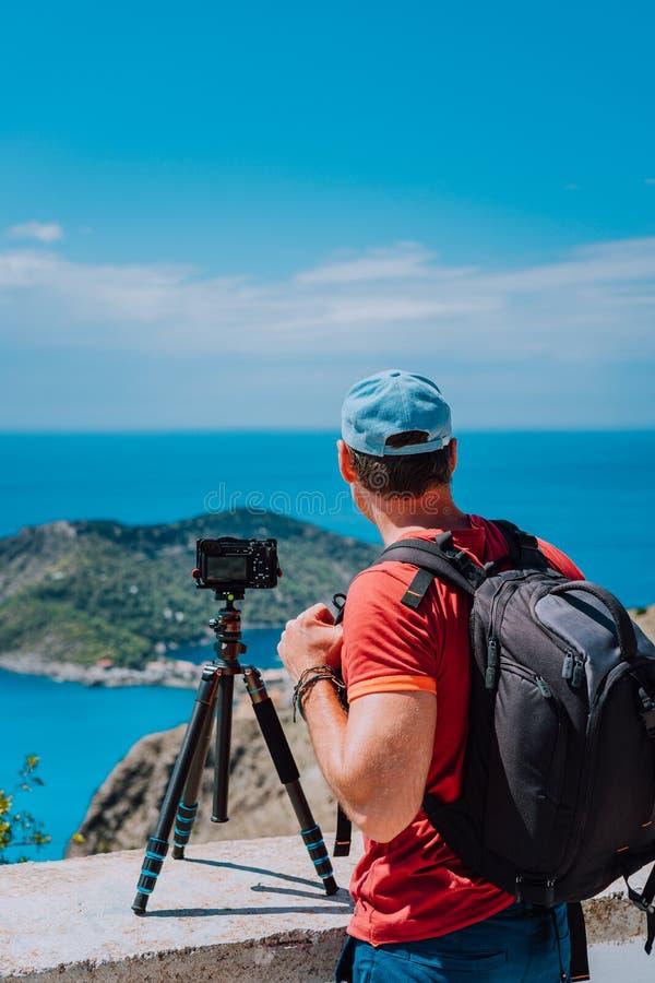 Мужской фотограф с рюкзаком наслаждаясь взглядом к деревне Assos во время изображения захвата от пункта взгляд сверху Камера даль стоковое изображение rf