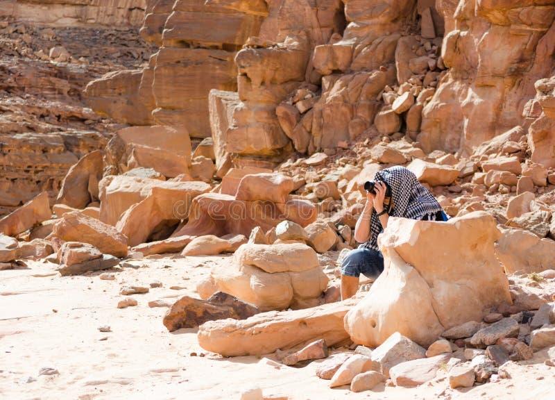 Мужской фотограф фотографирует сидя за камнем в каньоне в Египте Dahab южном Синай стоковые изображения rf