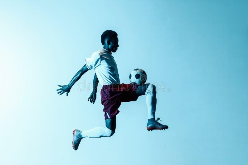 Мужской футболист пиная шарик в скачке изолированный на предпосылке градиента стоковые фотографии rf