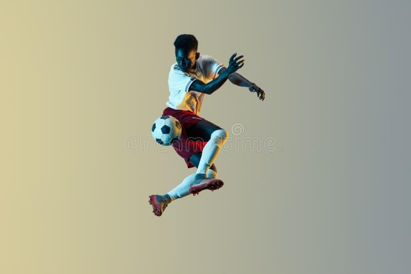 Мужской футболист пиная шарик в скачке изолированный на предпосылке градиента стоковая фотография rf
