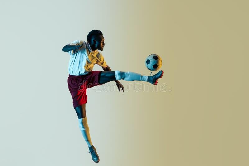 Мужской футболист пиная шарик в скачке изолированный на предпосылке градиента стоковая фотография