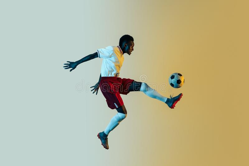 Мужской футболист пиная шарик в скачке изолированный на предпосылке градиента стоковые фото
