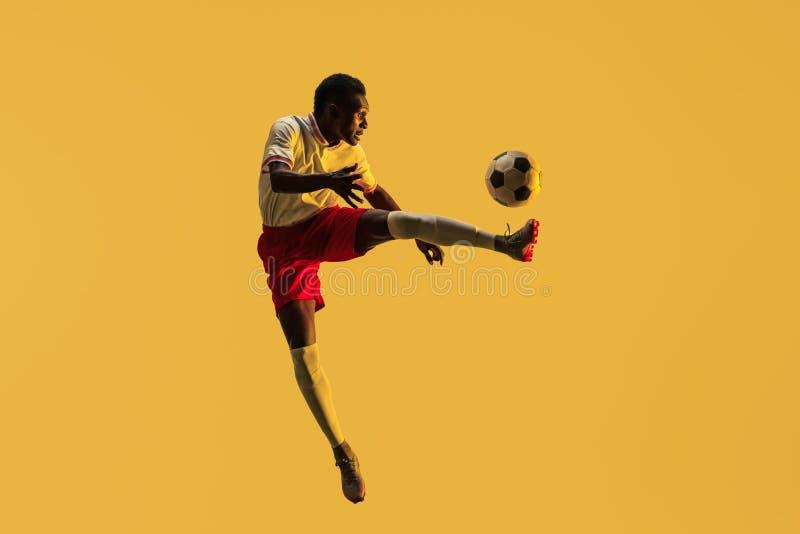 Мужской футболист пиная шарик в скачке изолированный на предпосылке градиента стоковые изображения rf