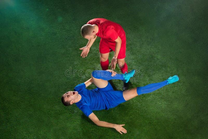 Мужской футболист страдая от травмы ноги на поле зеленого цвета футбола стоковое фото