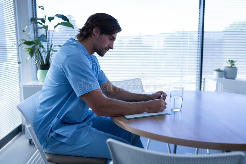 Мужской хирург смотря медицинскую диаграмму в больнице стоковые изображения