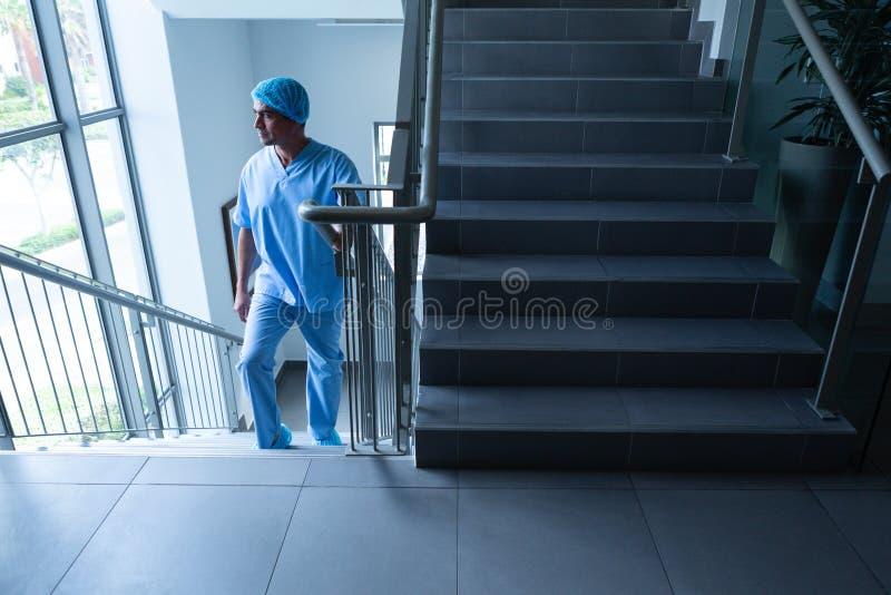 Мужской хирург смотря через окно пока взбирающся вверх лестницы больницы стоковое фото