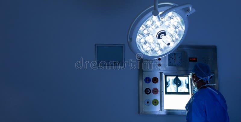 Мужской хирург читая луч x в операционной на больнице стоковое изображение rf
