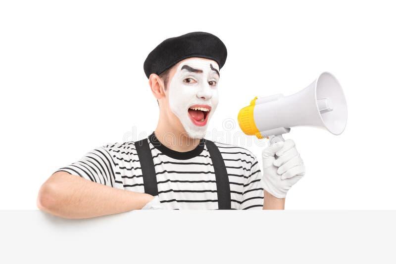 Мужской художник пантомимы держа громкоговоритель и представляя на пустом лотке стоковые фото