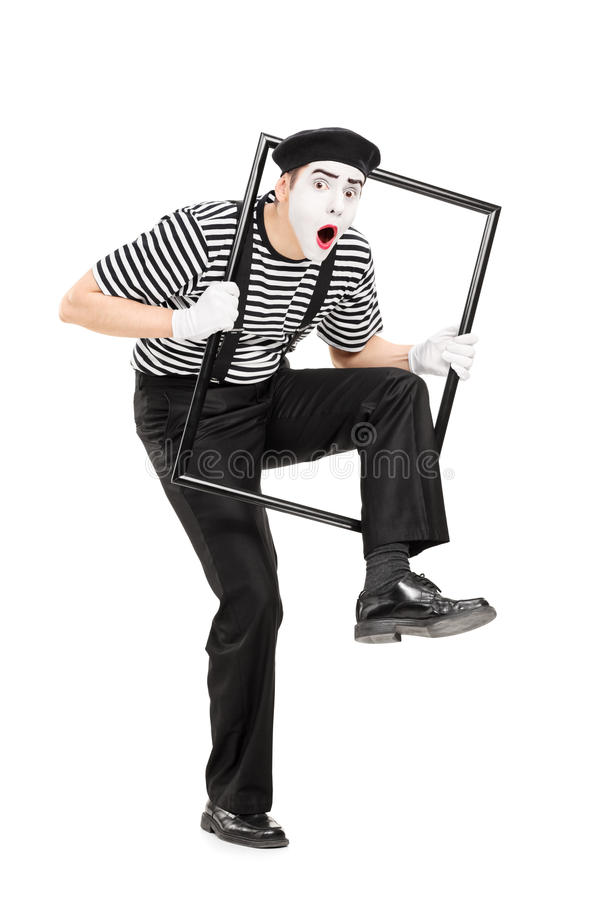 Мужской художник пантомимы идя через рамку металла стоковое фото rf