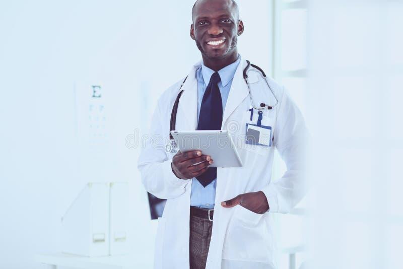 Мужской черный работник доктора при планшет стоя в больнице стоковые изображения rf