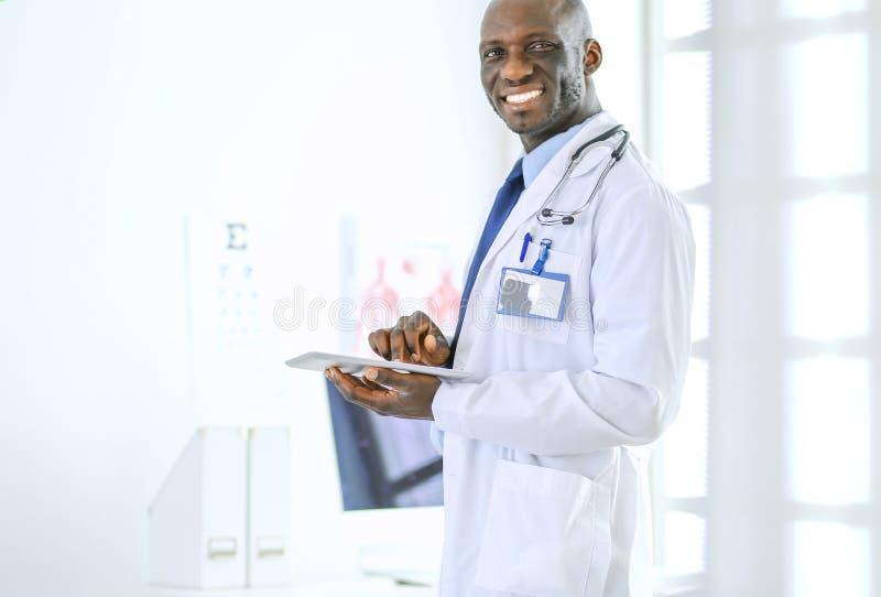 Мужской черный работник доктора с положением планшета в больнице стоковое фото