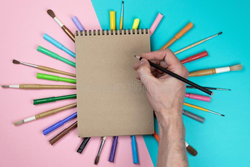 Мужской чертеж руки, чистый лист бумаги и красочные карандаши Клеймя сцена модель-макета канцелярских принадлежностей, пустые объ стоковые изображения