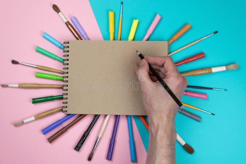 Мужской чертеж руки, чистый лист бумаги и красочные карандаши Клеймя сцена модель-макета канцелярских принадлежностей, пустые объ стоковые фотографии rf
