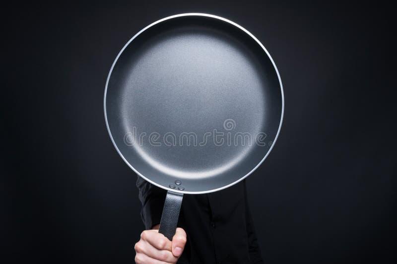 Мужской шеф-повар пряча за сковородой стоковые изображения