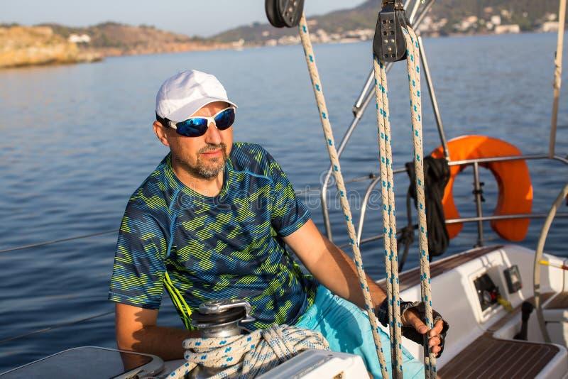Мужской шкипер сидя на его яхте плавания около такелажирования Спорт стоковое фото rf