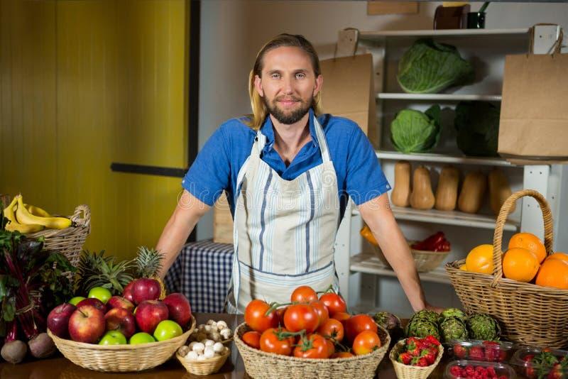 Мужской штат стоя близко vegetable счетчик на органическом разделе в рынке стоковая фотография