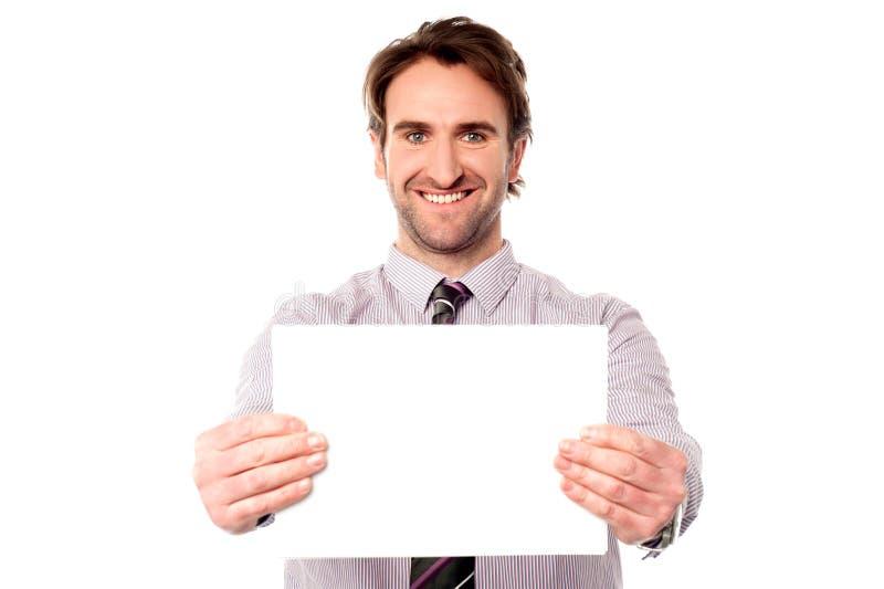 Мужской экзекьютив держа вне пустую доску объявления стоковая фотография rf