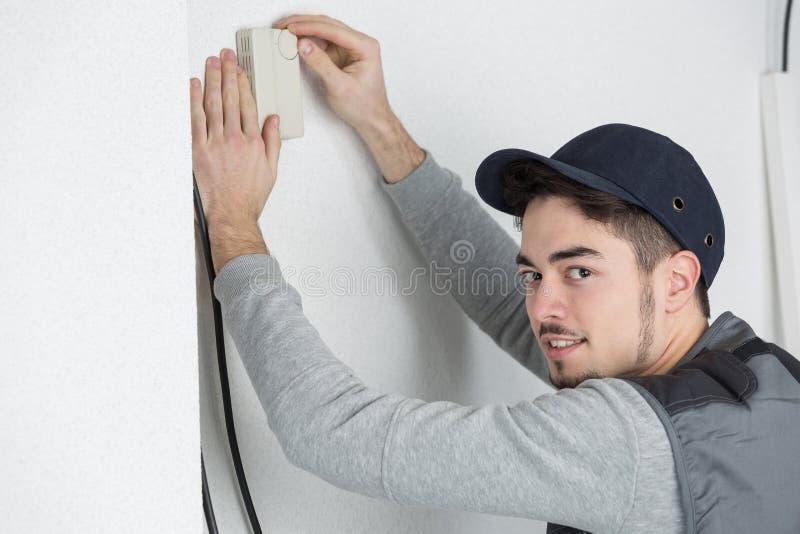 Мужской электрик при отвертка ремонтируя датчик огня стоковая фотография