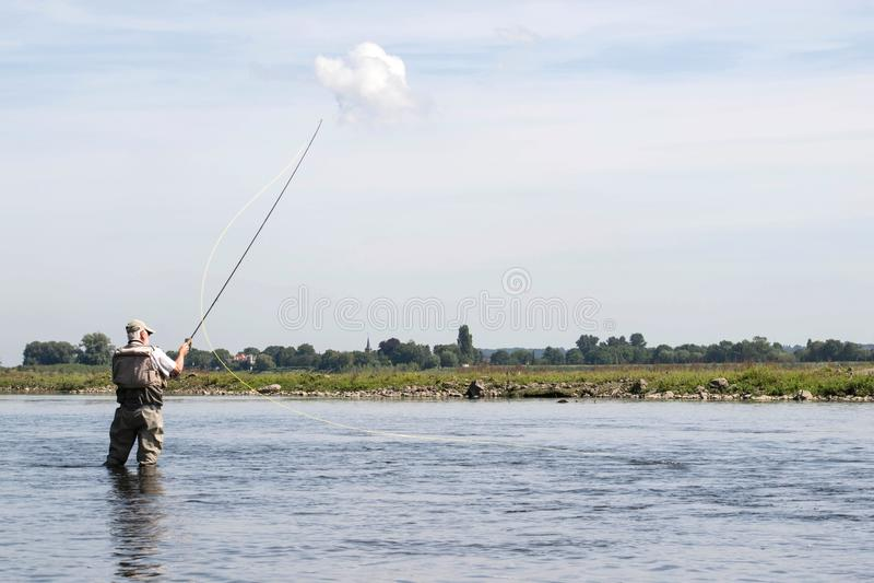 Мужской fisher стоя в реке с рыболовными принадлежностями мухы стоковая фотография