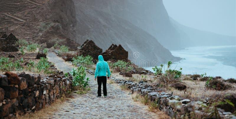 Мужской hiker восхищая красивый драматический ландшафт изрезанной береговой линии на trekking следе к Cruzinha Накидка Santo Anta стоковая фотография