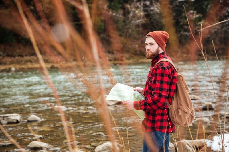 Мужской hiker держа карту и смотря отсутствующий outdoors стоковая фотография