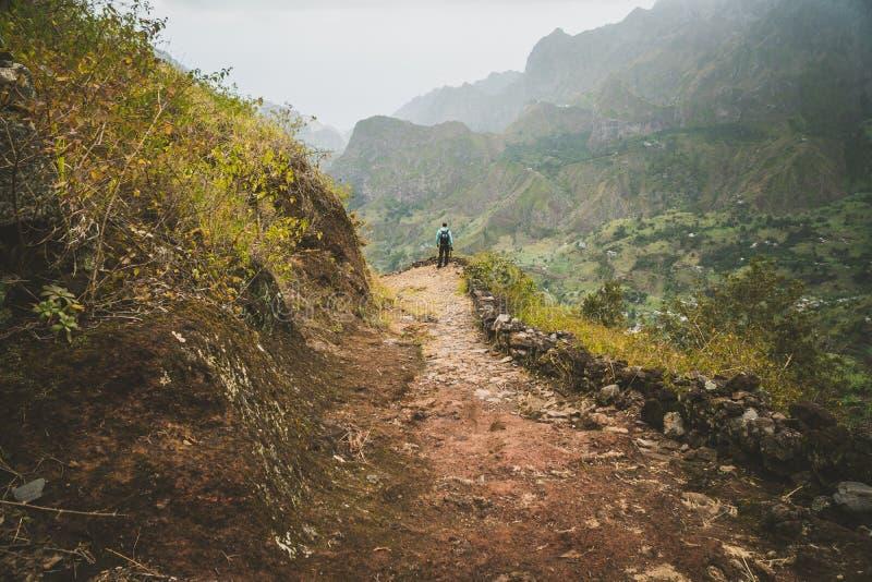 Мужской hiker наслаждаясь впечатляющим mountainscape Долина каньона плетки удлиняет далеко ниже Santo Antao, Cabo Verde стоковое изображение
