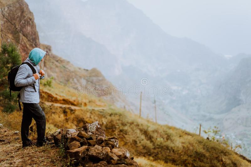 Мужской hiker смотря вниз к долине Xo-Xo Остров Santo Antao, Кабо-Верде Путешественник на пешем туризме скалы гор наслаждается ла стоковое фото