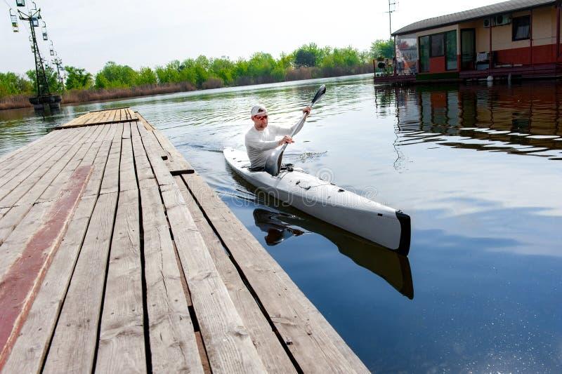 Мужской oarsman canoeing на озере используя затвор в летнем дне стоковые фотографии rf