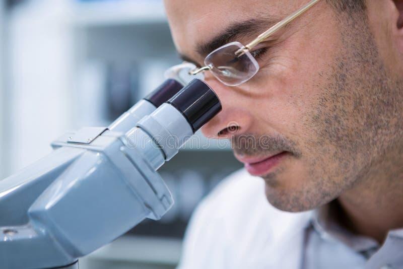 Мужской optometrist смотря через микроскоп стоковое изображение