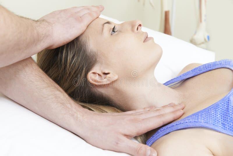 Мужской Osteopath обрабатывая женского пациента с проблемой шеи стоковое изображение rf