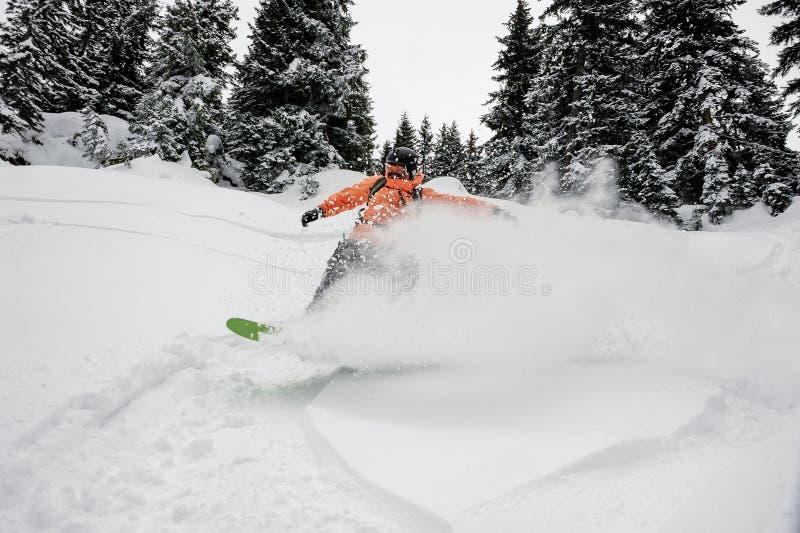 Мужской snowboarder бежать вниз с холма горы на сноуборде стоковая фотография
