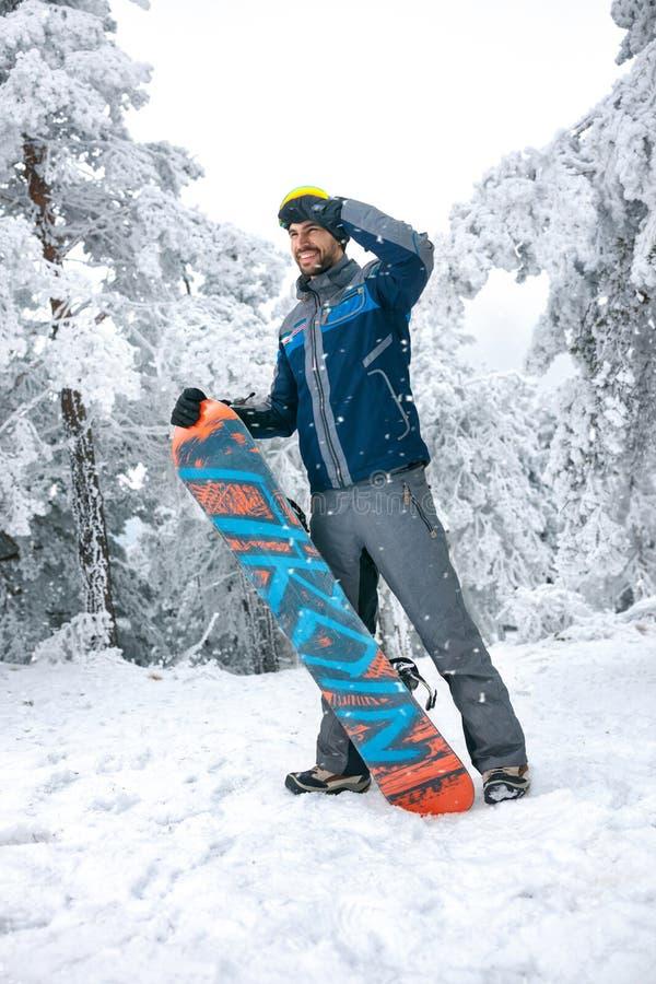 Мужской snowboarder смотря расстояние на местности лыжи стоковые фото