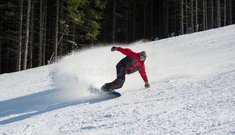 Мужской snowboarder сползает вниз от горы стоковое изображение rf