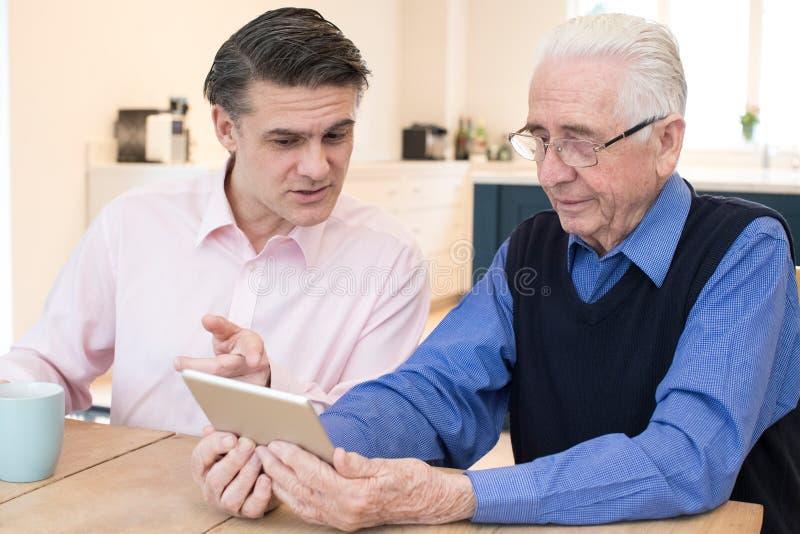 Мужскому человеку соседа показывающ старшему как использовать таблетку цифров стоковое фото