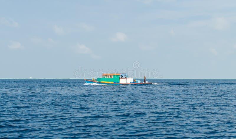 МУЖЧИНА, †«ноябрь 2017 МАЛЬДИВОВ: яркая красочная рыбацкая лодка в Индийском океане, около мужчины, Мальдивы стоковые изображения