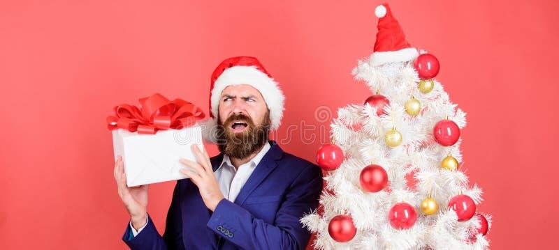 Мужчина бородатый хипстер формальный костюм christmas дерево держать подарочный ящик разделяя доброту и счастье Подготовьте подар стоковые фотографии rf