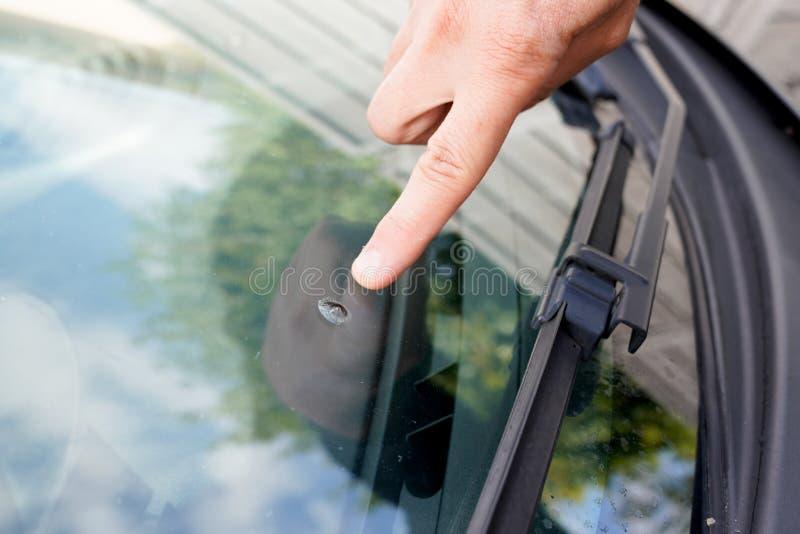 Мужчина видит автомобильную аварию, поврежденную каменным ветровым стеклом, во время управления автомобилем стоковое фото