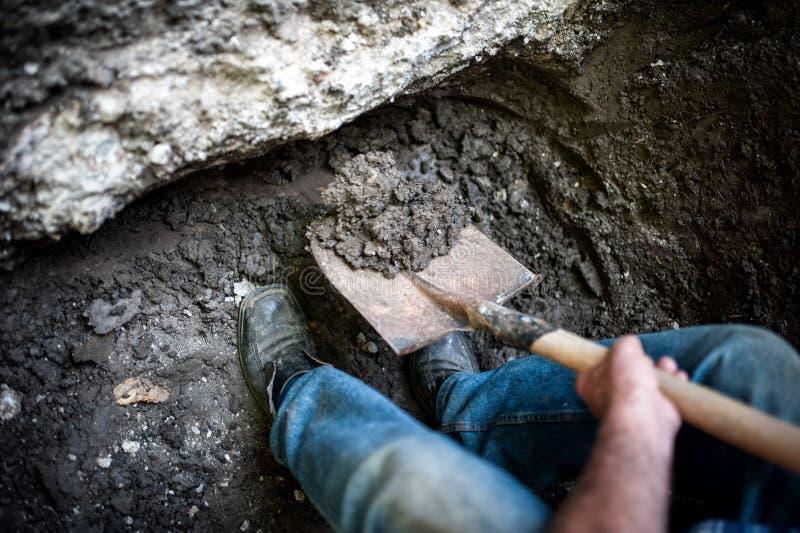 Мужчина выкапывая отверстие в земле с лопаткоулавливателем и лопатой стоковая фотография rf