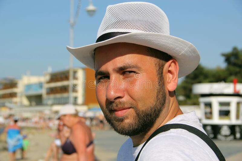 Мужчина в белой шляпе на пляже стоковые фото